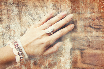 Image of beautiful female hand with ethnic ornaments on a background of ancient stone wall.