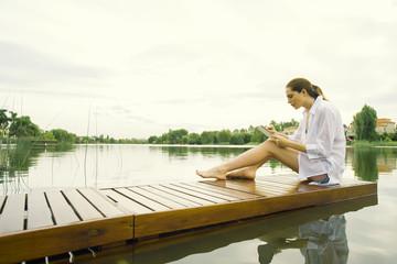Woman sitting on lake dock using digital tablet