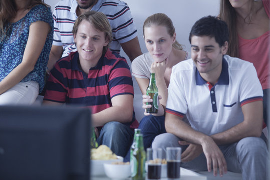 Friends watching sports match on television together