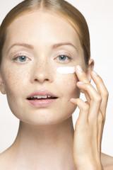 Young woman applying moisturizer under eye