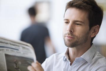 Mid-adult man reading newspaper, portrait