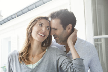 Couple sharing moment together by open window