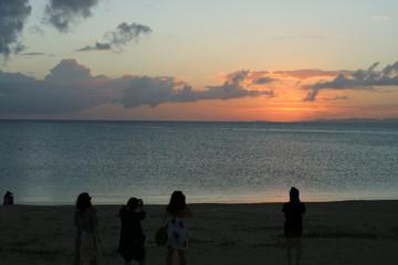 夕焼け空を写真に収める女性達
