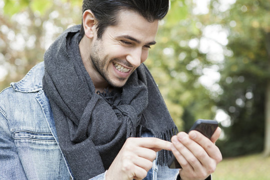 Young man using smartphone outdoors