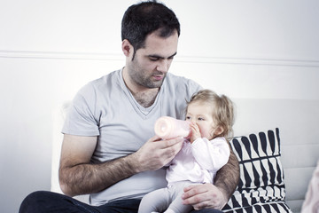 Father holding baby girl on lap, feeding her with bottle