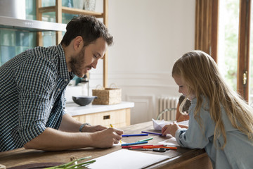 Father and daughter painting at home