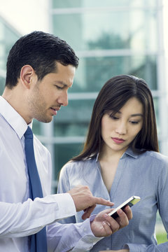 Business colleagues looking at smartphone