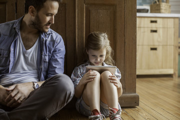 Father watching as daughter plays video game