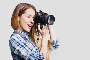 Woman photographer takes images with dslr camera. Isolated on gray background