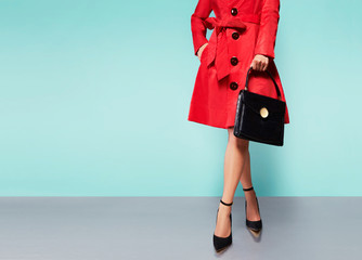 Woman with red trench coat isolated. Winter fashion image with bag and shoes.