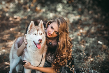 Girl playing with her husky dog in the park, autumn. Fashion blonde stylish woman. Outdoors. Beauty nature. Farytale.
