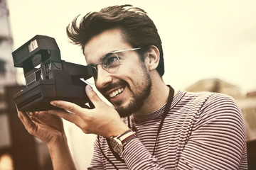 Happy man using a vintage camera