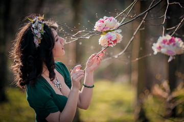 outdoor portrait of a beautiful brunette woman in green dress and wreath among blossom apple trees