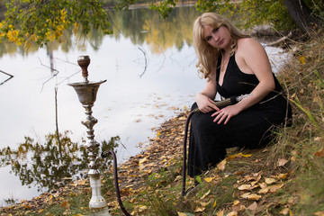 sexy blonde with big breasts smokes a hookah on the nature