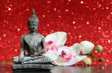 Buddha statue and a orchid flower on a bright red shiny glitter background with bokeh