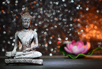 Zen Buddha statue and a lotus flower on a bright shiny glitter background with bokeh