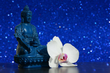 Buddha statue and a orchid flower on a bright blue shiny glitter background with bokeh