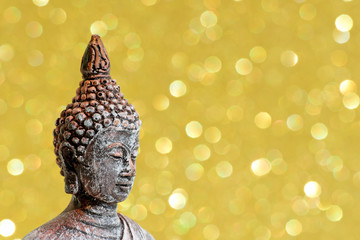 Zen Buddha statue on a bright gold shiny glitter background with bokeh