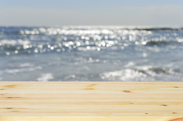 Empty wooden table top used for display or montage your products. In the background blurred sea and sky