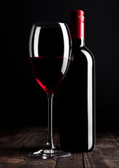 Red wine bottle and glass on wooden table black