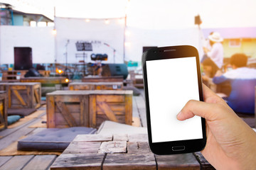 Hand holding smart mobile phone on outdoor cafe and light blurred background