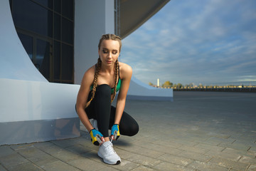 Concept: healthy lifestyle, sport. Attractive happy girl fitness trainer do outdoor workout at modern downtown urban area during sunset.