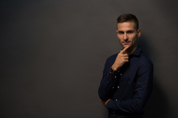 Cheerful man with short haircut touching his bearded face and smiling. Fashion or vogue concept. Magazine concept. Happy smiling model man in black shirt looking at camera isolated on black background