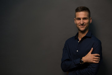 Picture of happy man posing over black background and posing for photographer. Handsome man smiling for camera with his hands crossed, folded, etc. Fashion or vogue concept.