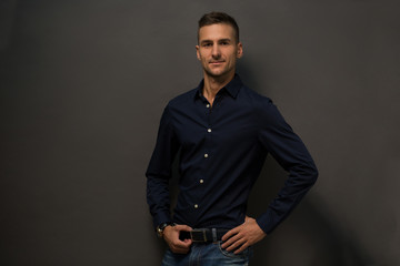 Happy man with short haircut looking at camera. Fashion or vogue concept. Magazine concept. Picture of mans face with different positive emotion while he is posing over grey background in studio.