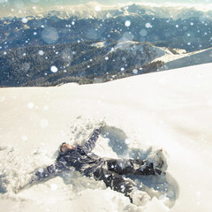 Happy woman making snow angel in the snow mountain. Ski.