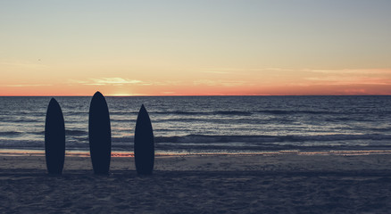Retro  photo of a  silhouette of surfboards on the  beach at sunset