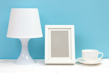 lamp, photo frame and coffee cup on wooden table
