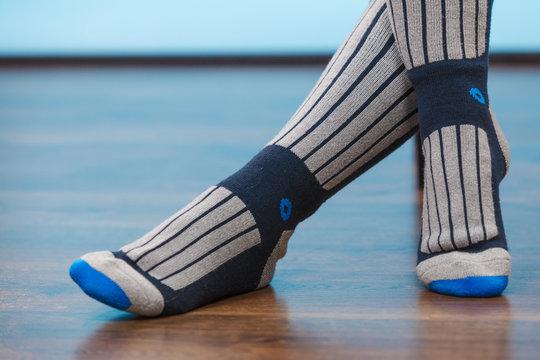 Woman legs in warm sporty socks on floor