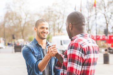 Two men giving a friendly handshake. A black man meeting his middle eastern friend and greets him in London. Friendship and lifestyle concepts.