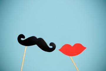paper heart shape fake lips and mustaches in sticks in front of blue background. vintage filtered image