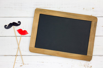 Paper heart shape fake lips and mustaches in sticks and blackboard in front of wooden white background. Wedding concept.