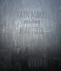 Rain drops on a window with wording Rain makes everything beautiful - Vintage effect style.