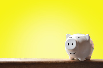 Piggy bank on yellow background. Soft focus
