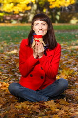 Smiling woman in autumn park with hot drink tea or coffee