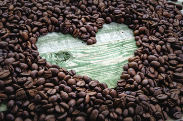 Heart in coffee beans on green wood table.