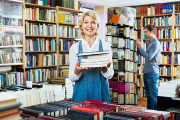 Smiling mature woman holding book pile in hands