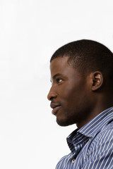Closeup profile of happy smiling Afro-American man in studio. Handsome man posing over white and looking away.