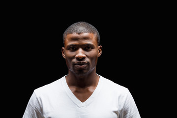 Portrait of handsome Afro-American man looking at camera in studio. Man in white T-shirt posing over black background.