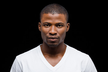 Closeup portrait of handsome Afro-American man posing in studio. Attractive man in white T-shirt over black background.