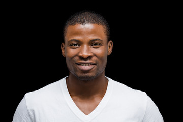Clack and white concepts. Portrait of Afro-American man posing over black background in studio. Handsome man smiling for camera.