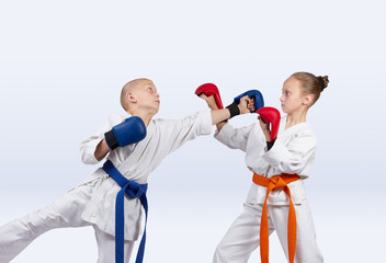 Boy beats punch girl standing in the rack karate