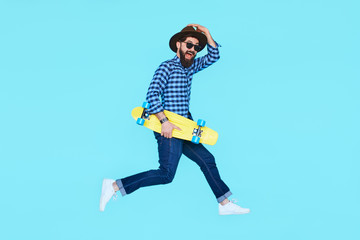 Pretty young bearded man jumping with yellow skateboard Wall mural