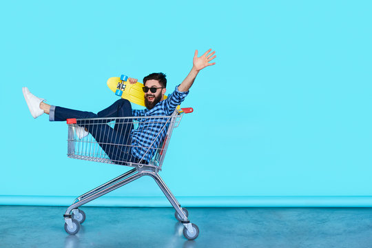 Side view of cheerful young man sitting in shopping cart