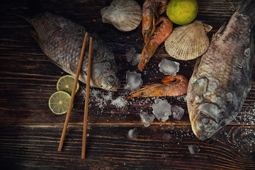 Food wooden background with Seafood, sticks, lime, salt. Copy sp