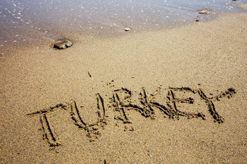 The word Turkey written in the sand on beach